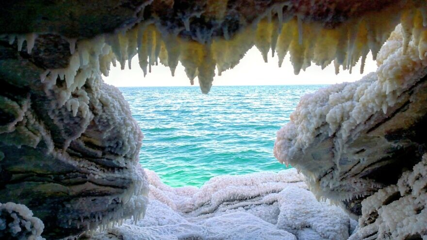 A view of the Dead Sea from inside a cave covered in salt and other minerals. Credit: Noam Bedein /deadsearevival.org.