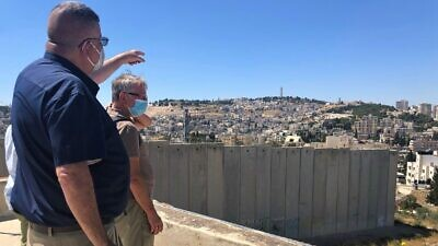 Ahmed Saleh Abu Hilal, mayor of Abu Dis, points past the security barrier towards Jerusalem. Photo by Eliana Rudee.