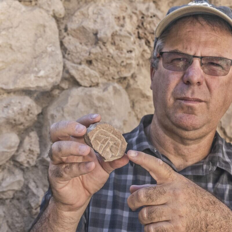 Professor Yuval Gadot from Tel Aviv University with the seal. Credit: Shai Halevy, Israel Antiquities Authority.