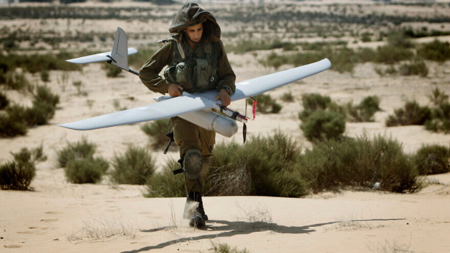 An Israeli soldier carries an unmanned aerial vehicle during a training drill at the Tze'elim army base on Aug. 5, 2013. Photo by Miriam Alster/Flash90.