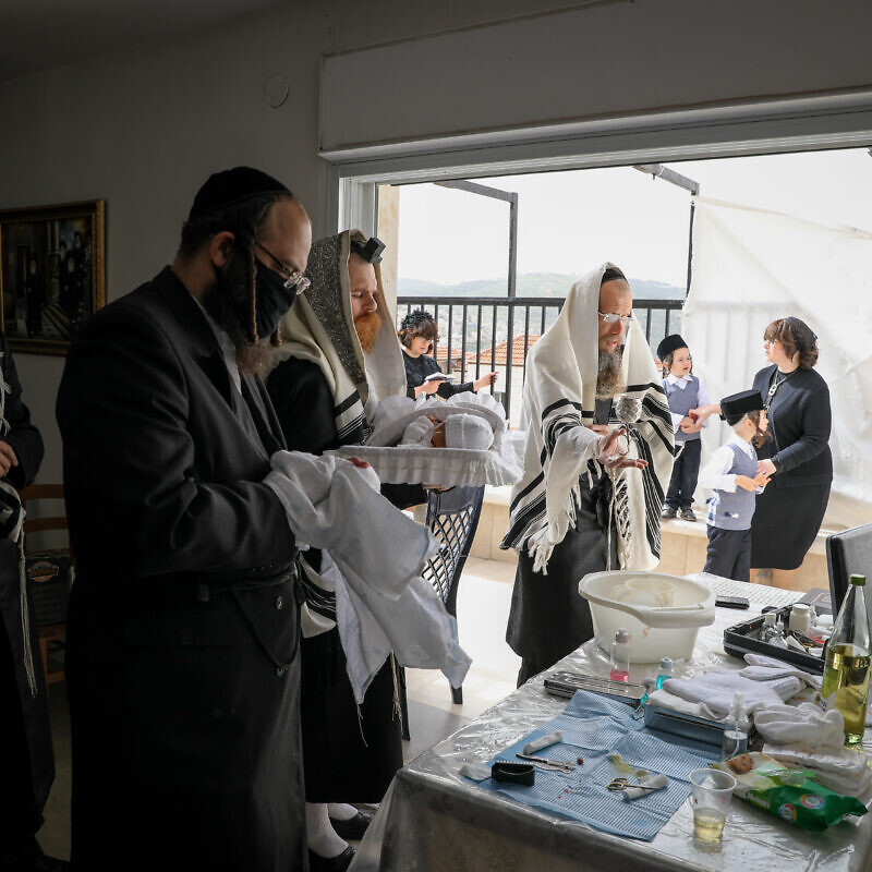 The Greenfeld family celebrate a brit milah at their home in Beitar Illit, Israel, on April 5, 2020. Photo by Nati Shohat/Flash90.