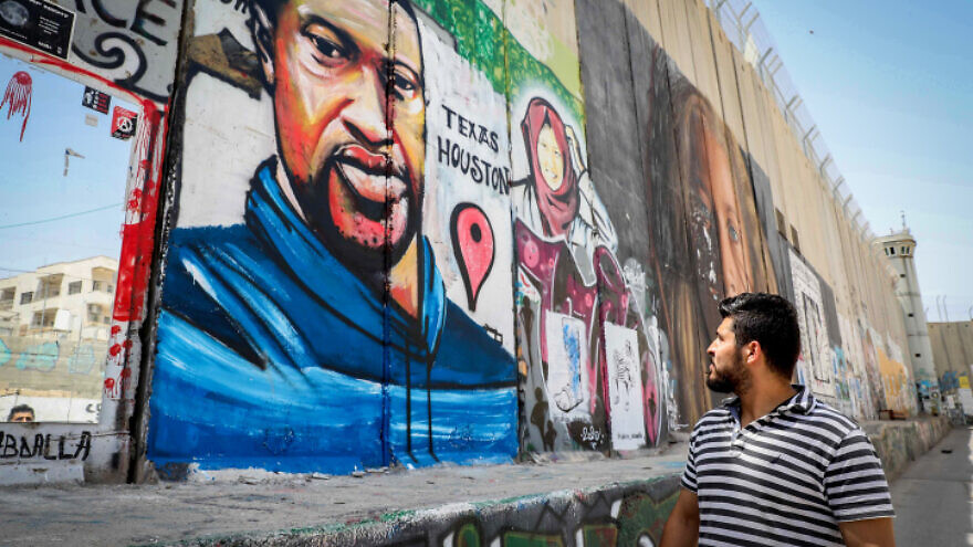 Palestinians walk past a mural of George Floyd painted on a section of the security barrier in the city of Bethlehem, on June 8, 2020. Photo by Wisam Hashlamoun/Flash90.