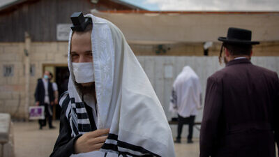 Jewish men pray outside a synagogue in Beitar Illit, Israel, on July 9, 2020. Photo by Nati Shohat/Flash90.