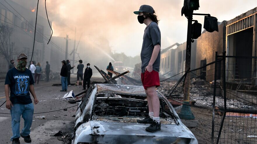 A man stands on a burned-out car on as fires burn behind him in the Lake Street area of Minneapolis days after the killing of African-American George Floyd at the hands of police, May 28, 2020. Credit: Lorie Shaull via Wikimedia Commons.