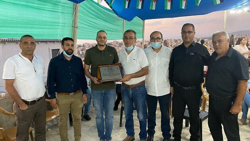 Joint Arab List Knesset member Sami Abou Shahadeh and a Balad delegation present convicted terrorist Anis Saffouri with a plaque following his release from prison. Source: Official Balad Facebook page.