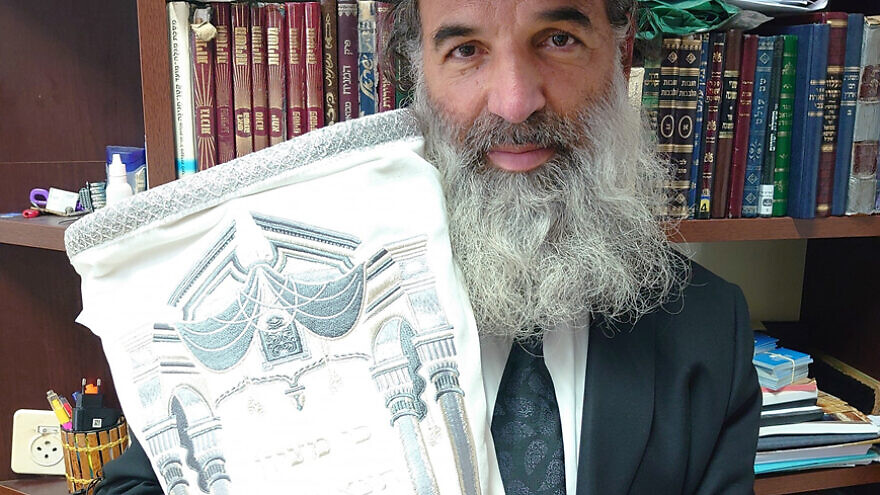 "Rabbi Avraham Goldstein, Director General and Rosh Yeshiva of The Mount Zion World Peace Center, holding ""The World Peace Torah"""