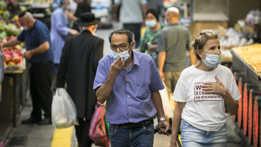 Israelis, wearing face masks for fear of the coronavirus, shop for grocery at the Mahane Yehuda market in Jerusalem on August 20, 2020. Photo by Olivier Fitoussi/Flash90