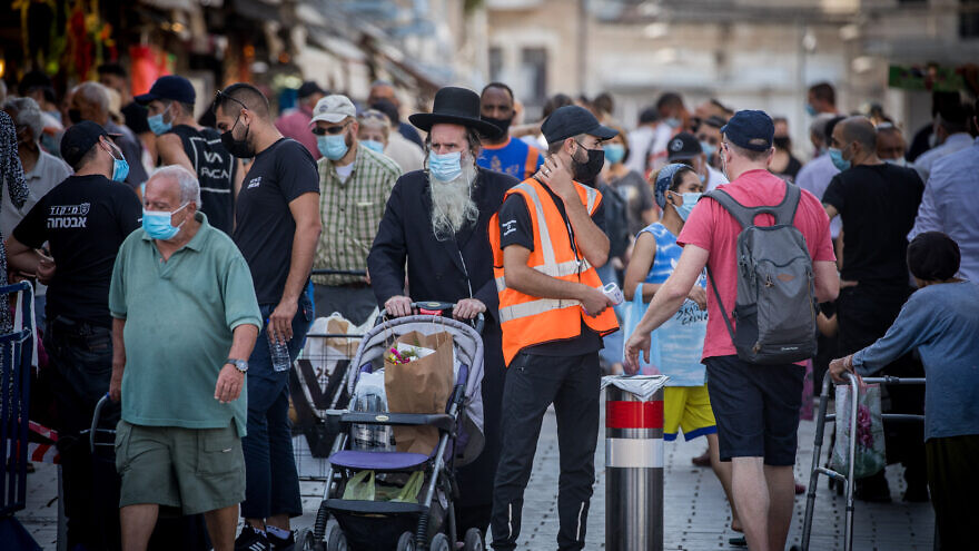 People wearing face masks shop at the Mahane Yehuda Market in Jerusalem on September 18, 2020, on the eve of the Jewish new year. Photo by Yonatan Sindel/Flash90
