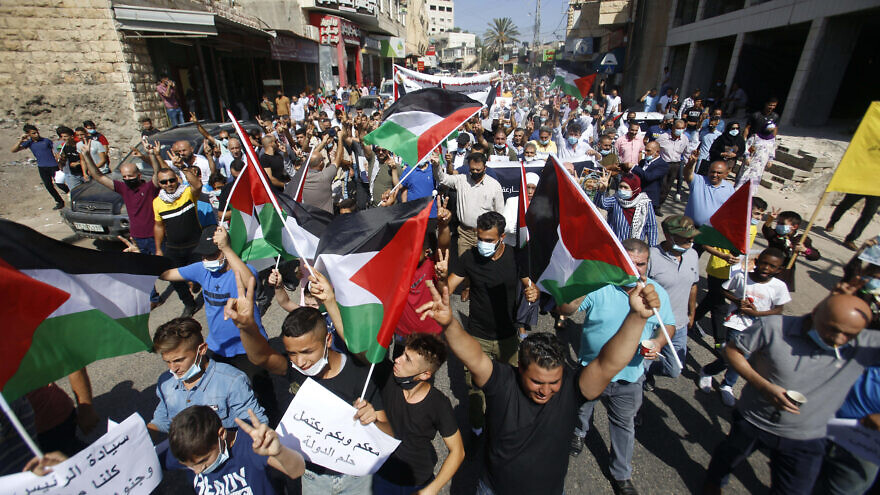 Palestinians hold flags during a rally in support of Palestinian Authority leader Mahmoud Abbas in the West Bank town of Tubas, Sept. 27, 2020. Photo by Nasser Ishtayeh/Flash90.