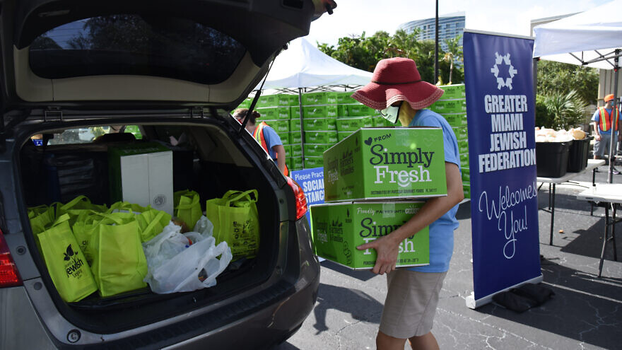Volunteers hand out food at a kosher drive-by distribution site sponsored by the Greater Miami Jewish Federation, Feeding South Florida, Jewish Community Services of South Florida and Temple Emanuel in July. Credit: Courtesy.
