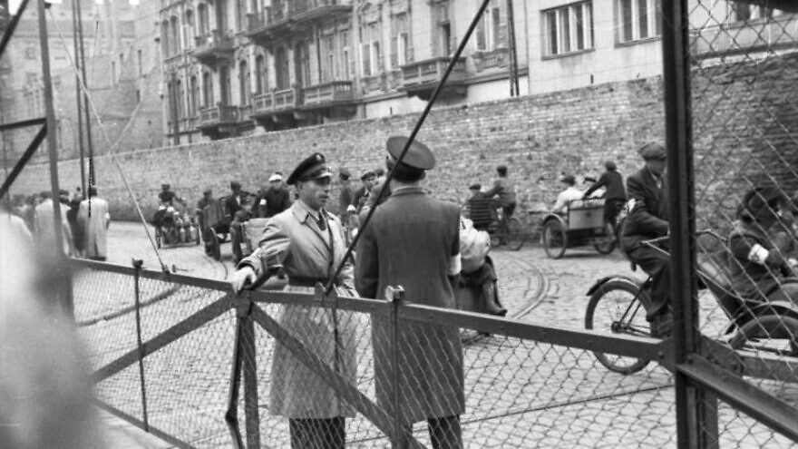Jewish Ghetto Police guarding the gates of the Warsaw Ghetto, June 1942. Credit: German Federal Archives via Wikimedia Commons.
