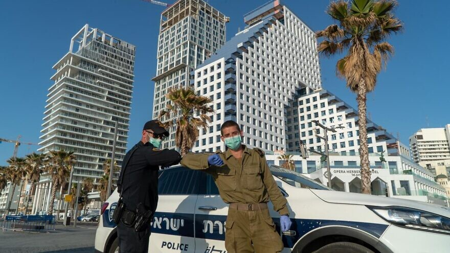 A IDF soldier and Israel Police do an elbow bump in front of one of the IDF Homefront Command''s coronavirus hotels in Tel Aviv. Credit: IDF Spokesperson's Unit.