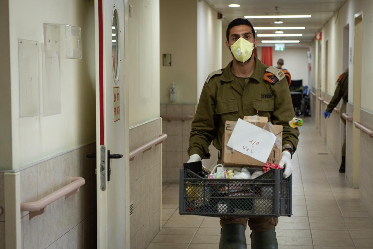 A soldier walking with supplies. Col. Michael Gilinski, the Jerusalem Home Front Command District Commander Chief Of Staff in reserve duty, told JNS that the hotels also host Israelis returning from abroad who have nowhere to isolate. Credit: IDF Spokesperson's Unit.