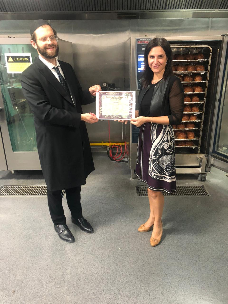 Rabbi Yissachar Krakowski with caterer Elli Kriel in the kitchen holding the kosher certificate for the event. Credit: Ross Kriel.