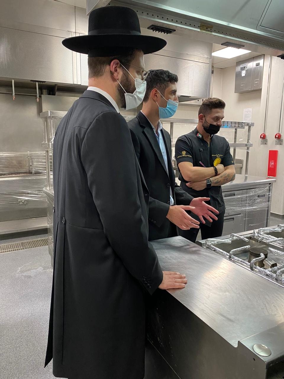 Rabbi Yissachar Krakowski examines the kitchen with a local mashgiach (kosher supervisor) and Khaled El-Shamzi, head of hospitality for the UAE's Ministry of Presidential Affairs. Credit: Elli Kriel.