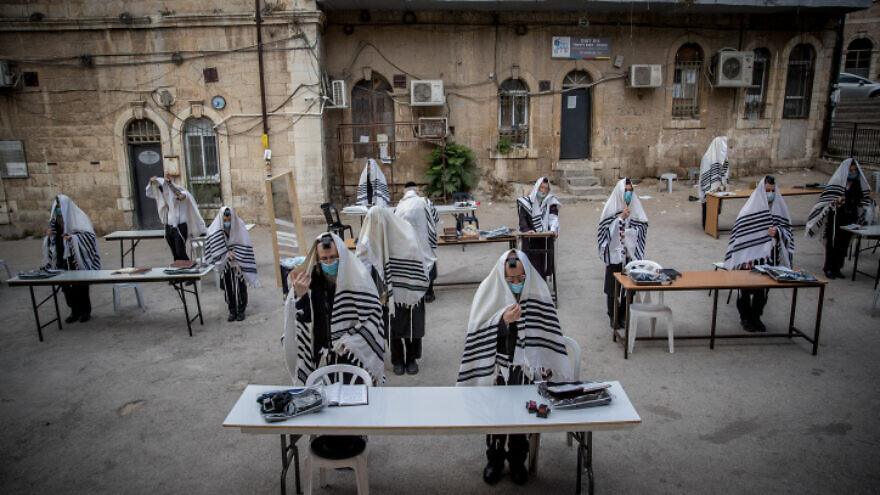 Chassidic Jews praying in accordance with social-distancing rules outside of their synagogue in Jerusalem on Aug. 10, 2020. Photo by Yonatan Sindel/Flash90.