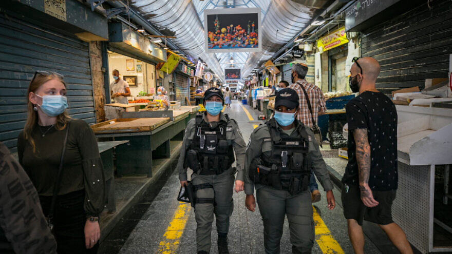 Israel Police officers patrolling Jerusalem's Machane Yehuda market during a nationwide COVID-19 lockdown, Oct. 4, 2020. Photo by Olivier Fitoussi/Flash90..