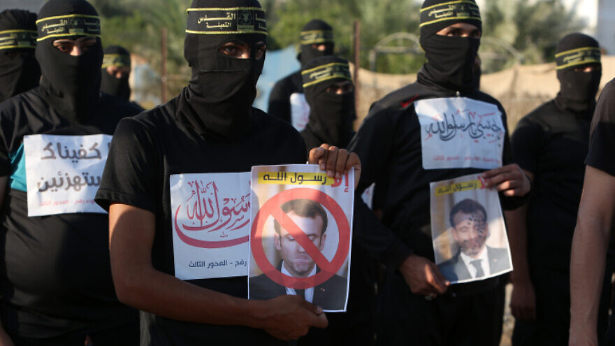 Members of the Al-Quds Brigades, the military wing of the Palestinian Islamic Jihad, hold pictures of French President Emmanuel Macron during a protest march in the southern Gaza Strip against the reprinting of a cartoon of the Prophet Muhammad in France, on Oct. 26, 2020. Photo by Abed Rahim Khatib/Flash90.