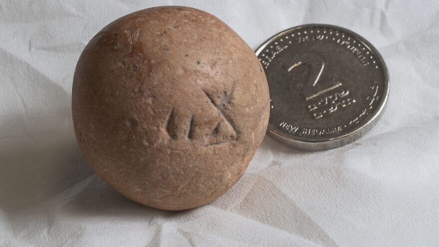 """A limestone """"two-shekel"""" weight, dating back to the Iron Age/First Temple period, discovered during excavations conducted by the Israel Antiquities Authority in conjunction with the Western Wall Heritage Foundation. It is seen here next to a modern two-shekel coin. Credit: Israel Antiquities Authority."""