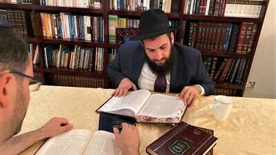 Rabbi Levi Duchman studies with a member of the UAE Jewish community at his synagogue. Credit: Chabad.org/News.