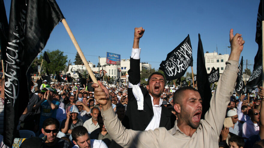 """Palestinian supporters of Hizb ut-Tahrir, or the Islamic Liberation Party, chant slogans and wave black and white flags reading """"There is no God but God, and Muhammad is his prophet"""" during a rally in Ramallah on July 7, 2012. Photo by Issam Rimawi/Flash90."""