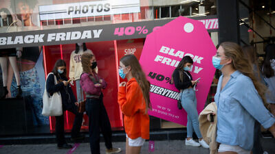 Israelis stand in line outside a clothing shop advertising Black Friday sales in Tel Aviv on Nov. 25, 2020. Photo by Miriam Alster/Flash90.