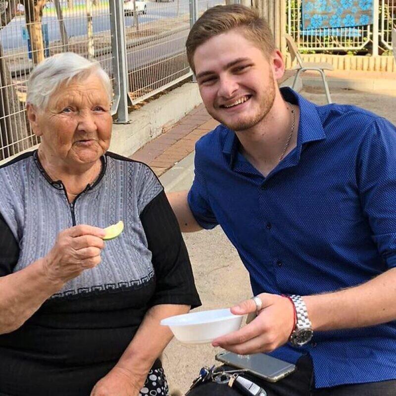 Yakov Pizenberg enjoys a snack with a senior citizen. Photo: Courtesy.