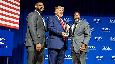 U.S. President Donald Trump is presented with an award by Florida State Rep. Byron Donalds (left) and Matthew Charles, one of the first inmates to benefit from the First Step Act of 2018, at the 2019 Second Step Presidential Justice Forum on Oct. 25, 2019, at Benedict College in Columbia, S.C. Credit: Official White House Photo by Shealah Craighead.