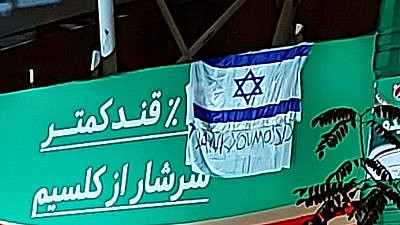 """An Israeli flag draped over a sign in Tehran that reads: """"Thank you, Mossad."""" Source: Twitter."""