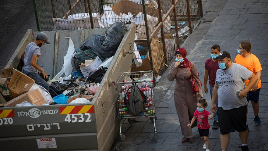 An Israeli teen rummages through a garbage bin in Jerusalem on Sept. 2, 2020. Photo by Nati Shohat/Flash90.