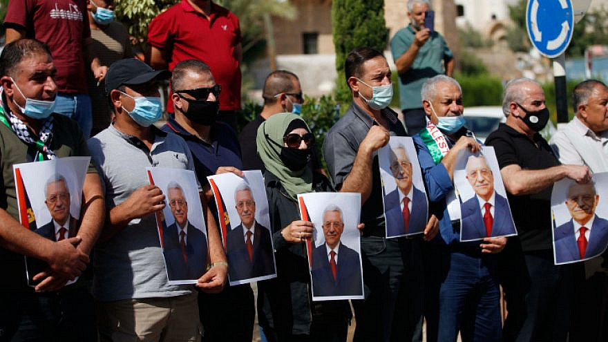 Palestinians hold photo printouts during a rally in support of Palestinian Authority leader Mahmoud Abbas in the West Bank town of Tubas on Sept. 27, 2020. Photo by Nasser Ishtayeh/Flash90.
