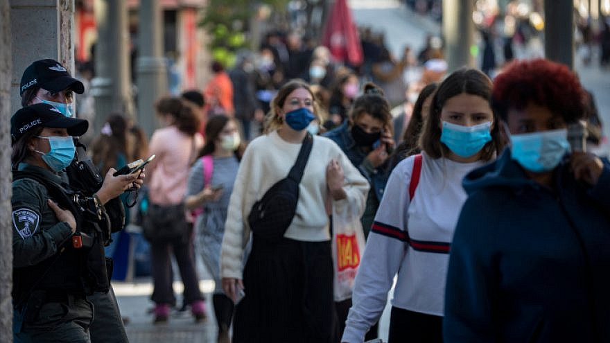 Jerusalemites wearing a face mask walk in Jerusalem City Center on November 29, 2020, as Israel steps out of coronavirus lockdown and rolls back restrictions. Photo by Olivier Fitoussi/Flash90