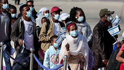 """New immigrants to Israel from Ethiopia's Jewish community arrive at Ben-Gurion International Airport as part of """"Operation Tzur Israel"""" (""""Rock of Israel"""") on Dec. 3, 2020. Photo by Miriam Alster/Flash90."""