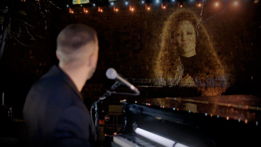 """An image of British singer Jess Glynne projected on the walls of Jerusalem's Old City, as she and Israeli musician Idan Raichel perform during """"Illuminate: A Global Jewish Unity Event,"""" to celebrate the Declaration of Our Common Destiny and Israeli President Reuven Rivlin's endorsement, Dec. 17, 2020. Credit: Courtesy."""