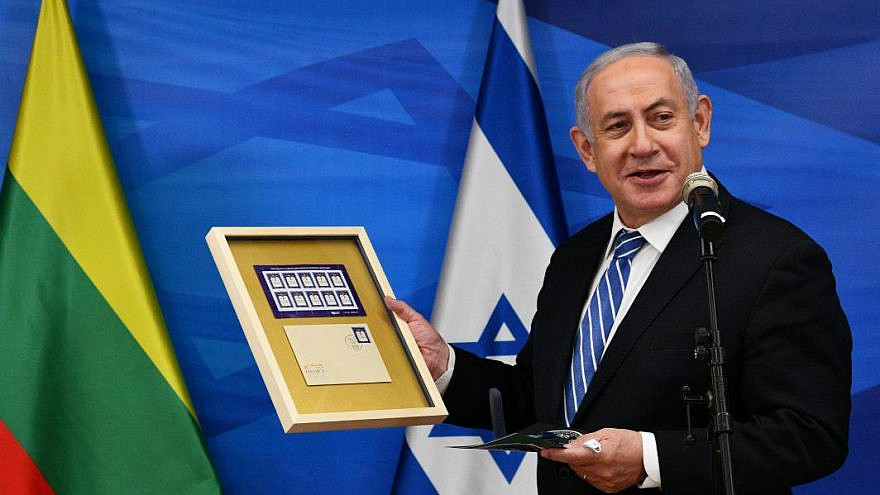 "Israeli Prime Minister Benjamin Netanyahu displays a frame containing special stamps issued by the Lithuanian postal authority within the framework of the ""Year of the Vilna Gaon,"" on Dec. 8, 2020. Credit: Haim Zach/GPO."
