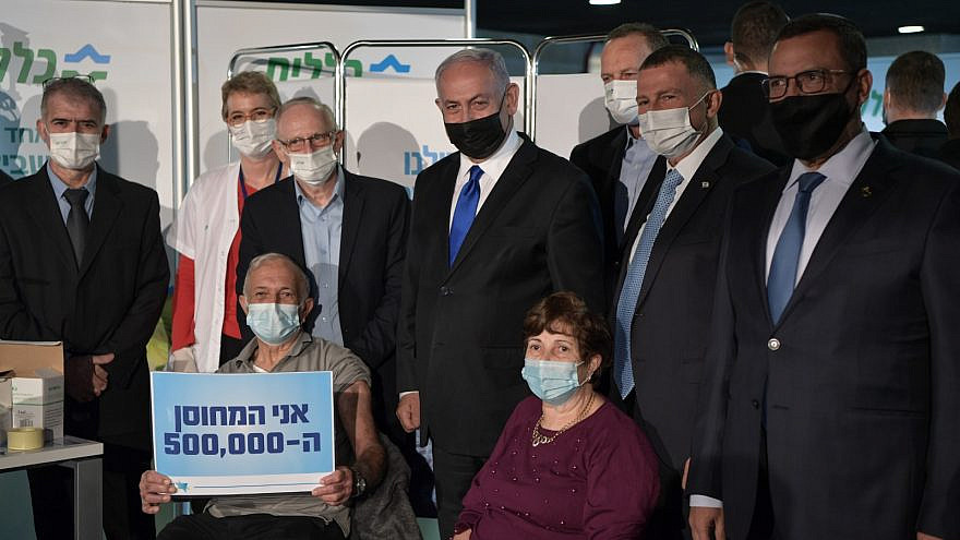 Israeli Prime Minister Benjamin Netanyahu and Health Minister Yuli Edelstein meet Herzl and Fadila Levy, the country's 500,000th people to be vaccinated against COVID-19, at a Clalit Health Services vaccination facility in Jerusalem on Dec. 29, 2020. Credit: Amos Ben-Gershom/GPO.