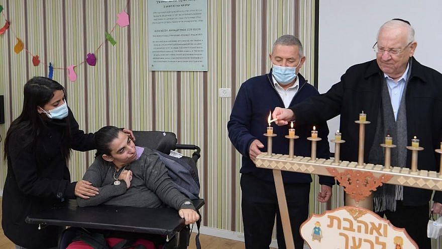 Israeli President Reuven Rivlin and Major General (Res.) Doron Almog light Chanukah candles at a special ceremony at the ADI Negev-Nahalat Eran rehabilitative village in Israel's south on Thursday, December 17, while a resident with severe disabilities looks on. (Photo credit: Amos Ben Gershom)
