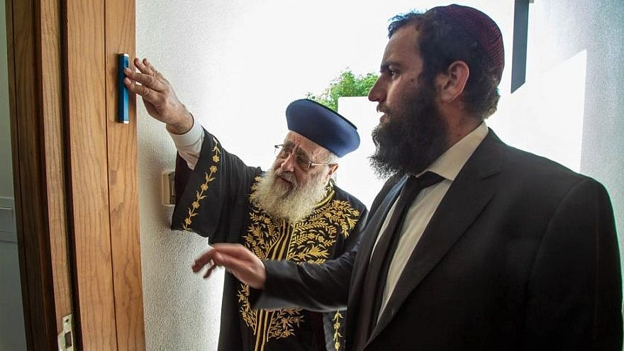 Israel's Chief Sephardi Rabbi Yitzhak Yosef affixes a mezuzah to a doorpost of the newly built Jewish school in the United Arab Emirates while on his first trip to an Arab country, as Chabad Rabbi Levi Duchman of the UAE looks on, December 2020. Credit: Courtesy of the Dubai Jewish Community Center.