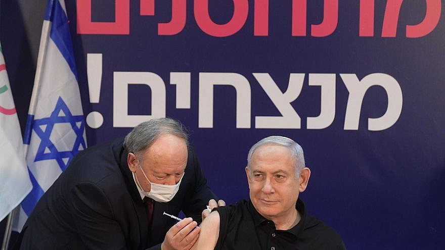 "Israeli Prime Minister Benjamin Netanyahu is inoculated against COVID-19 by his personal physician, Dr. Tzvi Herman Berkowitz, at Sheba Medical Center in Ramat Gan on Dec. 19, 2020. The text in the background reads: ""Vaccinate, win!"" Photo by Amos Ben Gershom/GPO."