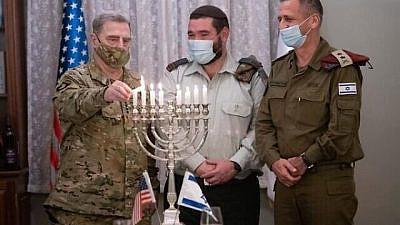 U.S. Chairman of the Joint Chiefs of Staff Gen. Mark Milley lights a menorah on the eighth night of Hanukkah alongside IDF Cpt. Josh Gerstein and IDF Chief of Staff Aviv Kochavi in IDF headquarters in Tel Aviv on Dec. 17, 2020. Credit: Israel Defense Forces.