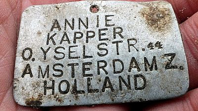 This ID tag was worn by Annie Kapper, a Jewish child from Amsterdam who was deported to the Sobibor extermination camp. Credit: Yoram Haimi/Israel Antiquities Authority.