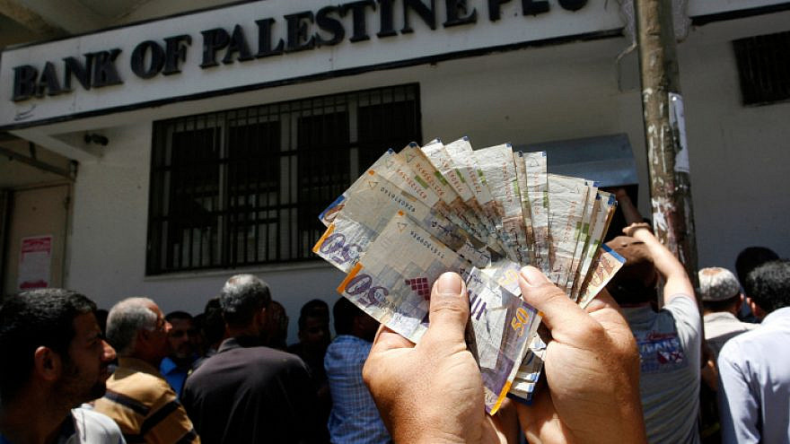 An employees of the Palestinian Authority displaying money he withdrew from a bank in Gaza City on June 11, 2014. Photo by Abed Rahim Khatib/Flash90.
