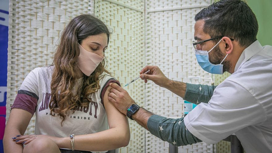 A young woman gets vaccinated at Clalit COVID-19 vaccination center in Rehovot on Jan. 4, 2021. Photo by Yossi Aloni/Flash90.