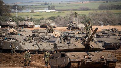 Israeli soldiers seen near IDF tanks stationed near the Israeli Gaza border on March 26, 2019. Photo by Yonatan Sindel/Flash90.