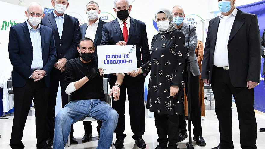 Israeli Prime Minister Benjamin Netanyahu, accompanied by Health Minister Yuli Edelstein (directly to his left), greeting Jabarin Muhammad (seated), the millionth citizen to receive the coronavirus vaccine, in Umm al-Fahm, Jan. 1, 2021. Credit: Haim Zach/GPO.