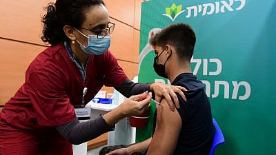 An Israeli student receives a COVID-19 vaccine in Tel Aviv after Israel approved vaccination of 11th- and 12th-graders, Jan. 23, 2021. Photo by Avshalom Sassoni/Flash90.