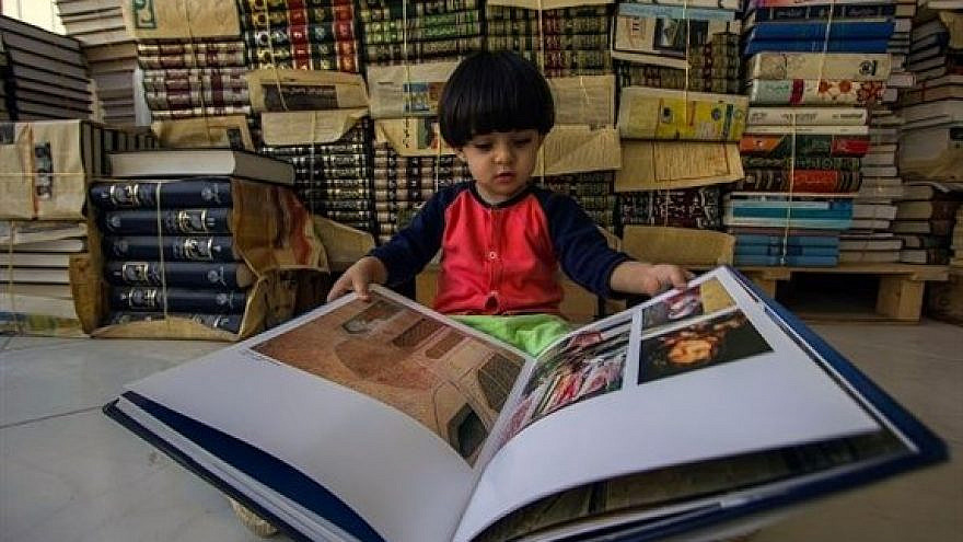 A child reading a book in Qom, Iran. Credit: Wikimedia Commons.