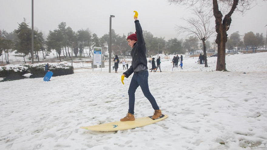 An Israeli teen uses a surfboard to play in the snow in Jerusalem on Feb. 18, 2021. Photo by Olivier Fitoussi/Flash 90.