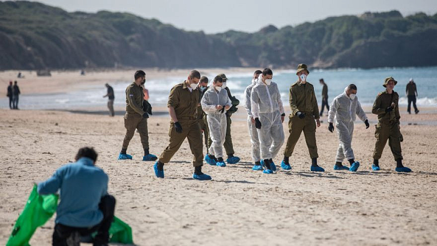 Israel Defense Forces soldiers clean tar off the Palmachim beach following an offshore oil spill that polluted much of the Israeli coastline, Feb. 22, 2021. Photo by Yonatan Sindel/Flash90.