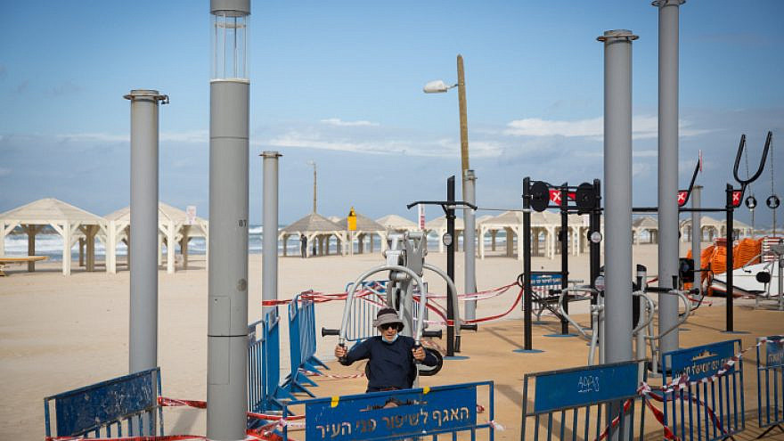 A man exercises at an outdoor gym on an empty beach in Tel Aviv during the nationwide lockdown on Jan. 17, 2021. Photo by Miriam Alster/Flash90.